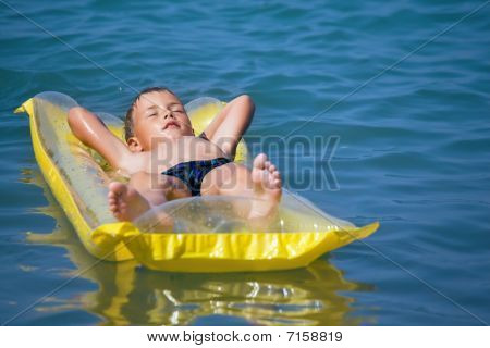 Boy In Dark Blue Swimming Trunks Relaxing On An Mattress