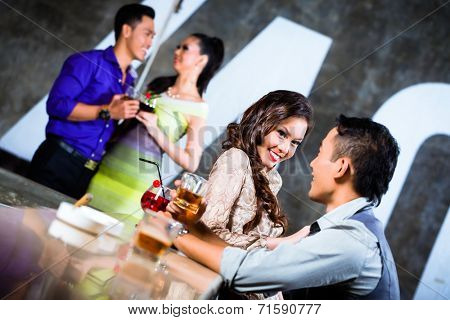 Two Asian young and handsome party people couples flirting and drinking at the bar in luxurious and fancy night club