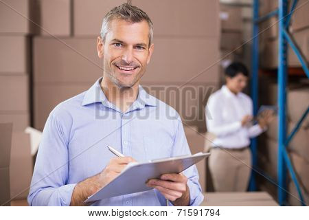 Warehouse manager writing on clipboard in a large warehouse