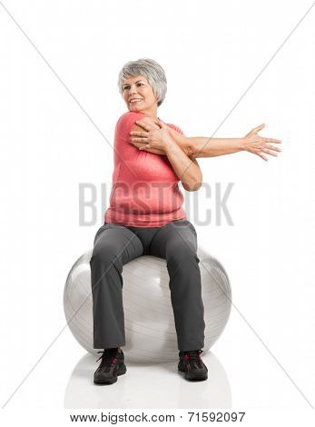 Happy fitness old woman making exercises with a PIlates ball