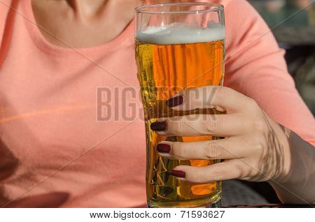 woman holding a glass of beer