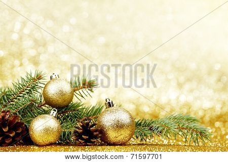 Christmas card with fir tree branch and decoration on golden glitter background