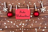 picture of weihnachten  - Red Label in the Snow Hanging on a Line with the German Words Frohe Weihnachten which means Merry Christmas  - JPG