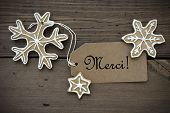foto of ginger bread  - The French Word Merci which means Thanks on a Label with Ginger Bread Snowflakes with White Decoration on Wooden Background - JPG