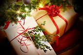 stock photo of greenery  - Christmas gifts with ribbons and bows under the tree - JPG