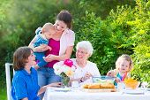 stock photo of little young child children girl toddler  - Happy grandmother enjoying a sunny summer day having lunch with her family  - JPG