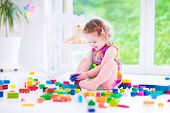 stock photo of brick block  - Adorable laughing toddler cute little girl with curly hair wearing a pink summer dress playing with colorful blocks and toys sitting on a floor in a sunny bedroom with a big window - JPG