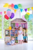 image of baby doll  - Adorable curly toddler girl in a white dress and her little baby brother playing together with a birthday present  - JPG