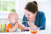 picture of solid  - Young attractive mother feeding her cute baby son giving him his first solid food healthy vegetable pure from carrot with a plastic spoon sitting in a white sunny kitchen at a window at home - JPG