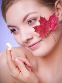 stock photo of capillary  - Face of young woman with leaf as symbol of red capillary skin on gray. Girl taking care of her dry complexion applying moisturizing cream. ** Note: Shallow depth of field - JPG
