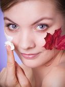 image of capillary  - Face of young woman with leaf as symbol of red capillary skin on gray - JPG