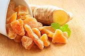 foto of home remedy  - Closeup dried candied crystallized ginger pieces and raw root on wooden table - JPG