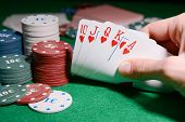 image of poker hand  - Chips and cards for poker in hand on green table - JPG