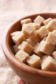 pic of sugar cube  - Brown sugar cubes in bowl on sackcloth background - JPG