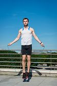 stock photo of skipping rope  - Young sport man exercising  - JPG