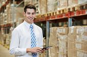 stock photo of dispatch  - smiling manager in warehouse with tablet pc computer  - JPG