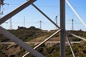 image of tarifa  - Look through electricity pole to landscape with wind turbines - JPG