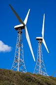 stock photo of tarifa  - Wind turbines on the green hill with blue sky - JPG