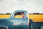 foto of truck farm  -  a handsome man with a cowboy hat on driving a truck past a field full of yellow flowers  - JPG
