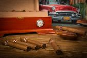 stock photo of cigar  - Cuban cigars and humidor with ashtray on rustic wooden table with Cuban painting of american old car in background - JPG