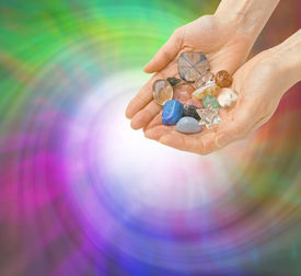 picture of semi-circle  - Crystal Healer with open palms cupped and holding a selection of healing crystals on a spiral green and purple colored swirling background - JPG
