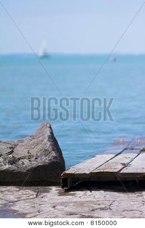 Roca y muelle en la playa