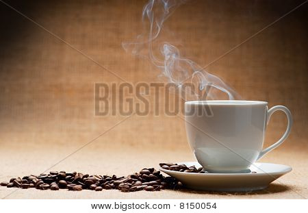 Cup Of Hot Coffee About The Ferry And Grains Of Coffee On Grunge A Background