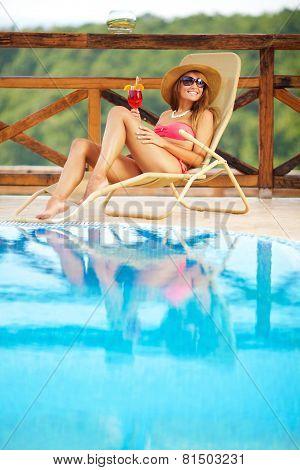 Beautiful Woman Enjoying By The Swimming Pool