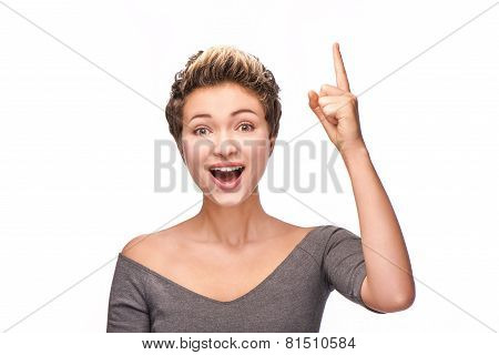 Cheerfully looking at camera young woman with finger up