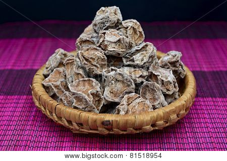 Salted Chinese plums in a bamboo basket