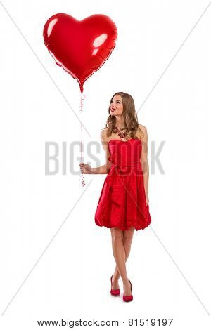 Attractive young girl in red dress holding Valentine's Day helium balloon