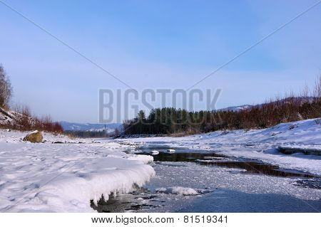 Winter river. Thawed on ice. Forest. Siberia. Khakassia.