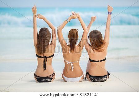 Girls in bikinis sunbathing, sitting on the beach.