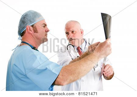 Doctors discussing x-ray results.  Focus on the older doctor pointing out a problem to his younger intern.  Isolated on white.