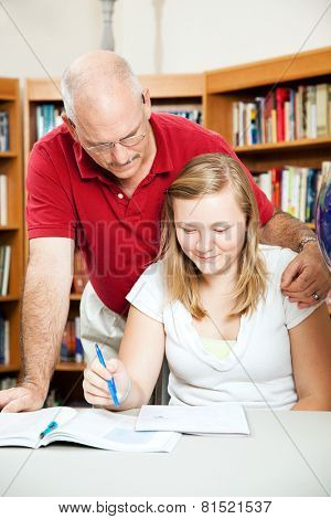 Father or teacher helping a teenage student at the library.