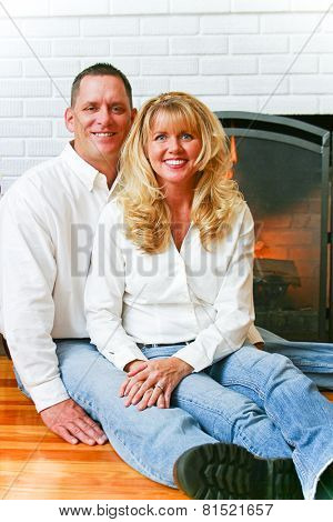 Portrait of a beautiful married couple at home in front of their fireplace.