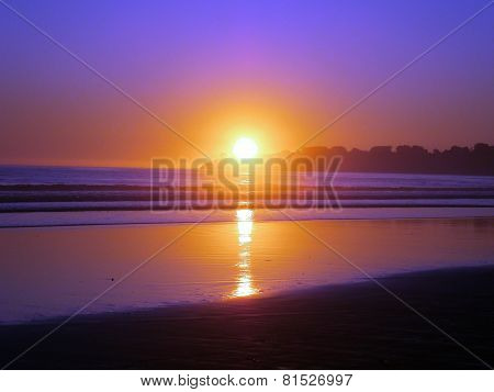 Epic Sunset Reflects On Ocean And Beach On An Empty Clear Sky Day