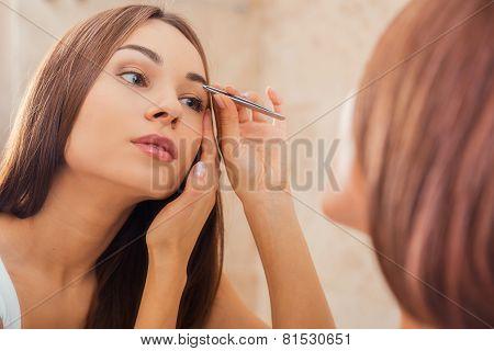 Tweezing Eyebrows.