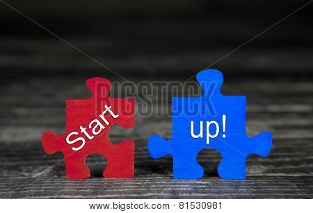 Business concept for start-up: red and blue puzzle on wooden background with text.