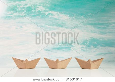 Business concept for challenge and movement: three paper boats on maritime turquoise ocean background.