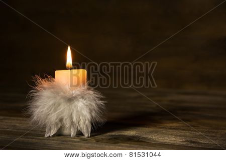 One burning candle with feathers on old wooden background.