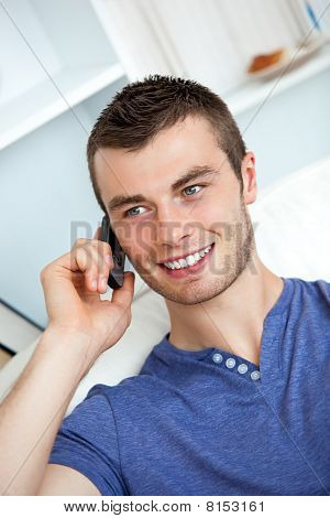 Attractive Man Sitting On Sofa And Talking On Phone