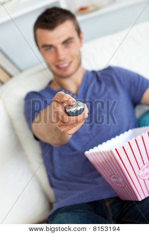Smiling Man Is Relaxing In The Living-room With Popcorn