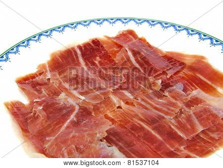 Closeup of serrano ham slices on a dish. Jabugo. Spanish tapa.