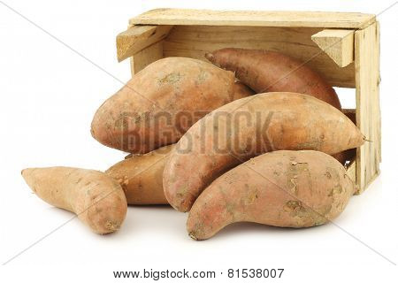 Sweet potatoes in a wooden crate on a white background
