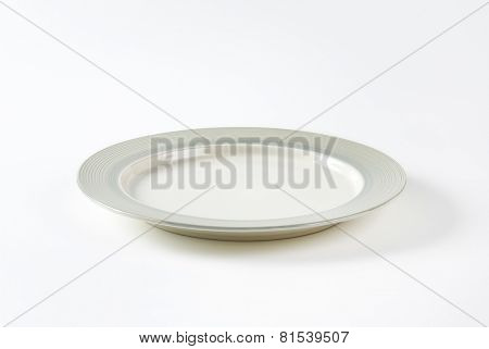 Charger plate with wide grey rim decorated with a pattern of subtle rings
