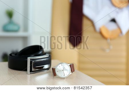Men's belt and watch with shits and tie on chair on background