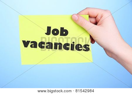Job Vacancies text on piece of paper in hand on blue background