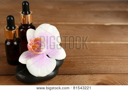 Spa composition with bottles of aromatic oils and orchid on wooden background