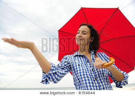 Woman With Umbrella Touching The Rain